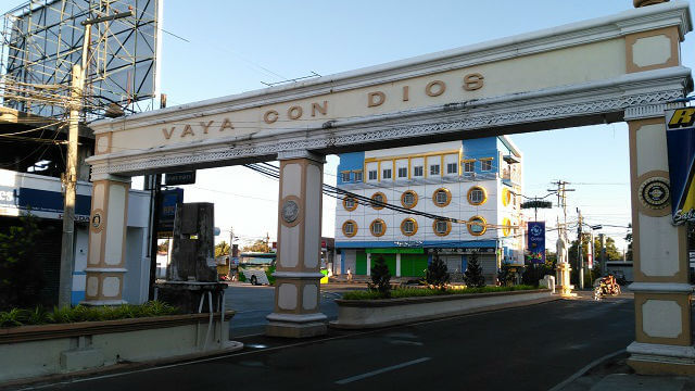 """Vaya Con Dios is literally translated to """"Go with God"""". A typical phrase to say goodbye in Spanish. Behind the arc is the Henady Inn at day time."""