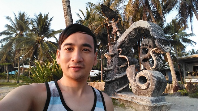 Selfie with a stone sculpture facing the boardwalk.