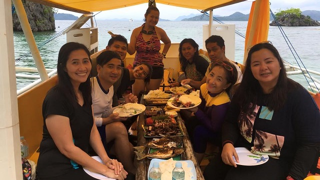 Fellow travelers having lunch in one of the islands in Coron during the island hopping tour.